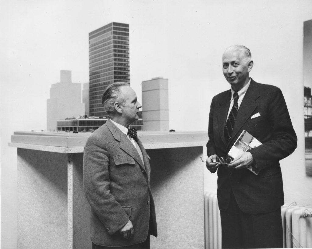 Schwarz-weiß-Aufnahme von Zwei äleren Herren im Anzug vor einem Architekturmodell
