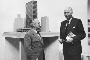 Black and white photo of two elderly men in a suit in front of an architectural model