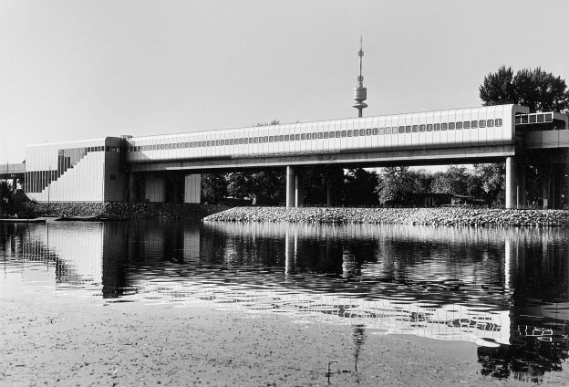 Elongated building with many windows on stilts over a water surface