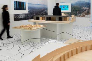 2 Personen in Ausstellung mit Modell und Bildschirmen