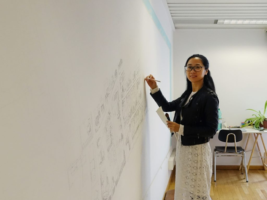 A woman with glasses draws a village on a white wall.