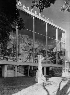 schwarz-weiß Bild einer Glasfassade, dahinter Aufnahmen eines Bergpanoramas, davor weiße Frauenskulptur