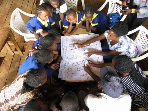 Mehrere sitzende Kinder und junge Erwachsene über Pläne gebeugt