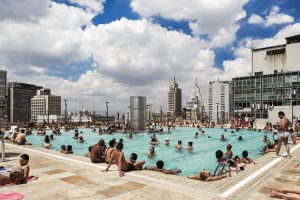 Swimming pool on a roof with bathing people and skyscrapers in the background