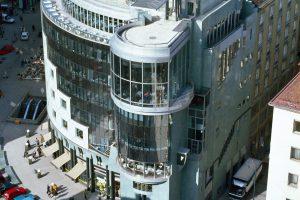 Mehrstöckiges halbrundes Gebäude mit Glasfassade und parkenden Autos davor