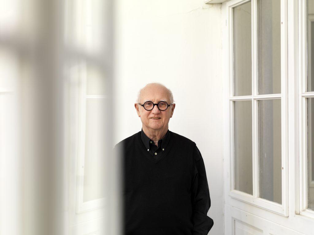 Älterer Herr mit Brille und schwarzem Hemd neben einer Türe