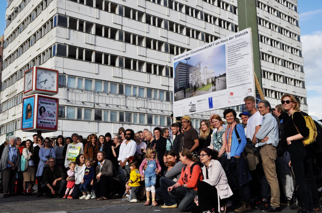a group of people posing for a photo in front of a multi-storey white skyscraper
