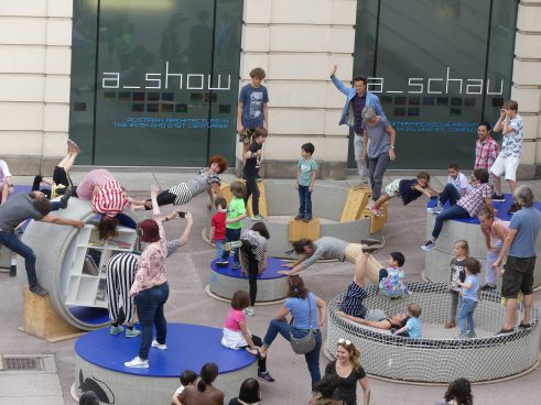Children and adults gymnastics on concrete rings