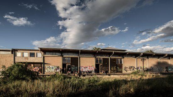 stillgelegtes einstöckiges Bahnhofsgebäude mit einer Wiese im Vordergrund