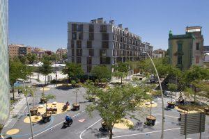 ein asphaltierter Platz mit Bäumen in Töpfen und Sitzgelegenheiten vor mehrstöckigen Wohnhäusern