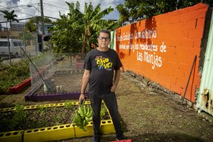 Black dressed man with glasses and bananas in his hand in front of plant beds