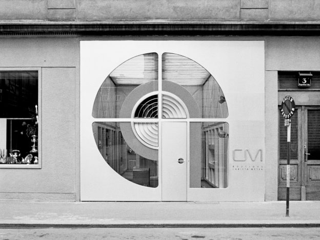 Black and white-photograph of a shop portal with an entrance door and a round shop window