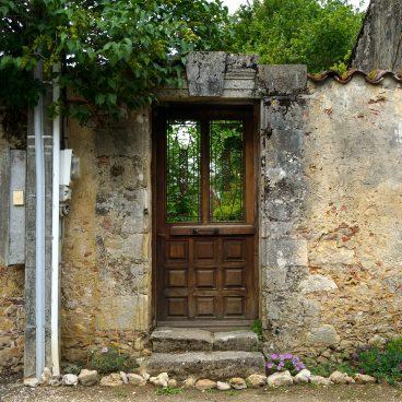 Holztüre mit Fenster in einer Mauer