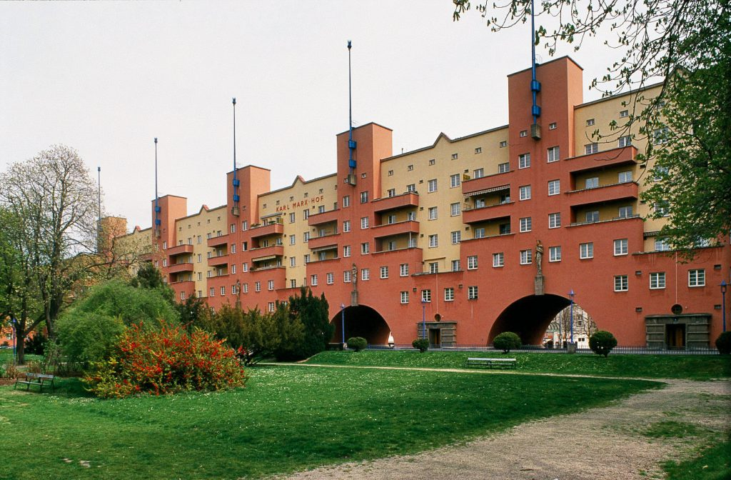 View of a multi-storey apartment block with yellow-red façade
