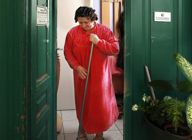 Woman with broom and red dress behind an open red door