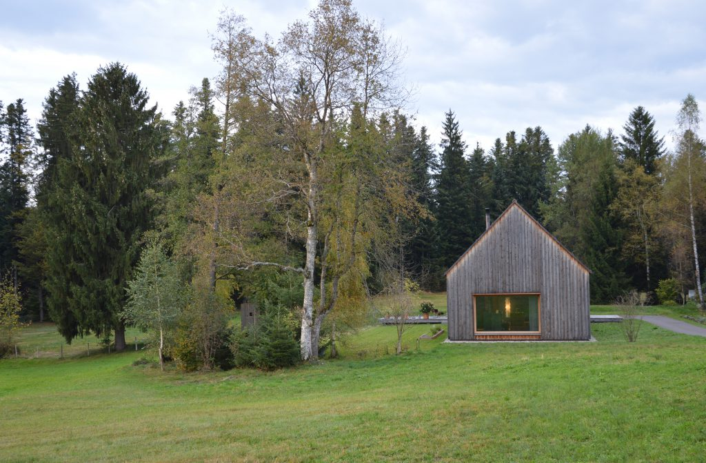 Wooden house with a large window and saddle roof on a meadow next to a tree and forest in the background