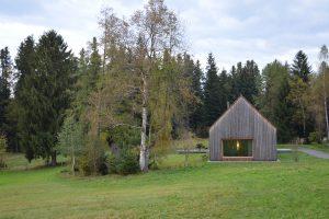Holzhaus mit eine großen Fenster und satteldach auf einer Wiese neben einem Baum und Wald im Hintergrund