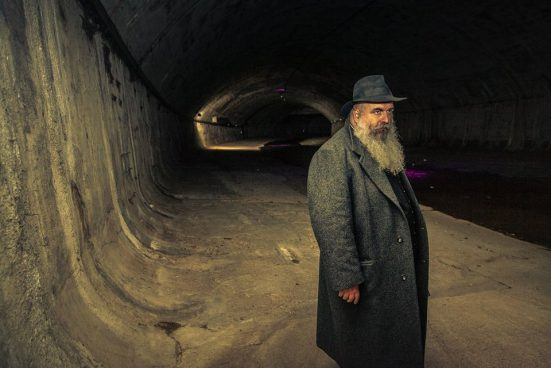 a man with a long grey beard and hat in a canal shaft