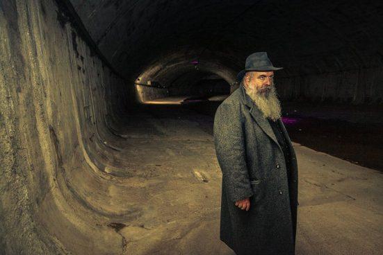 ein Mann mit langem grauen Bart und Hut in einem Kanalschacht