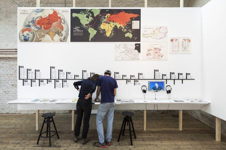 2 Personen vor großer Tafel in Ausstellung
