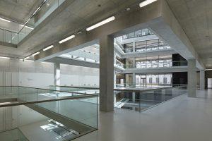 Innenraum mit Schacht und Galerien aus Beton und Glas