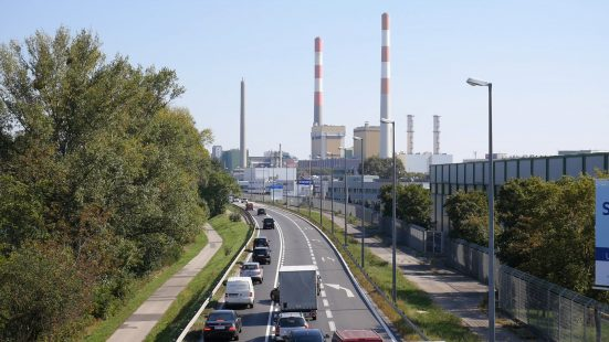 Cars on a multi-lane road and factory chimneys in the background