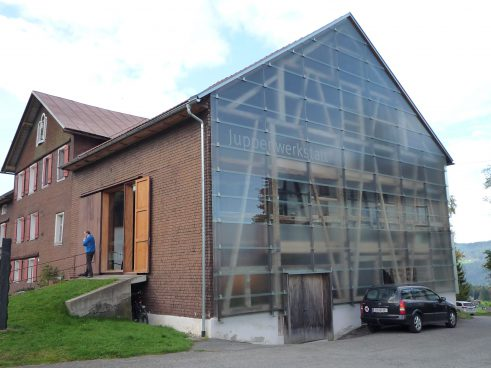 a house with shingle façade on the one hand and glass façade on the other hand