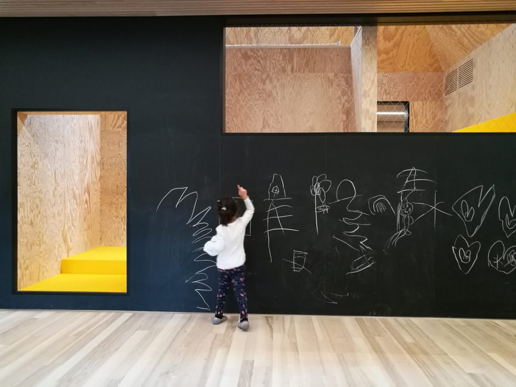 Child paints a black wall with a door opening and a window opening