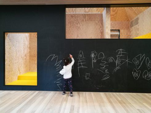 Kind bemalt schwarze Wand, die eine Tür- und eine Fensteröffnung aufweist
