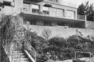 schwarz weiß Foto von Terrassenhaus mit 2 Stühlen davor