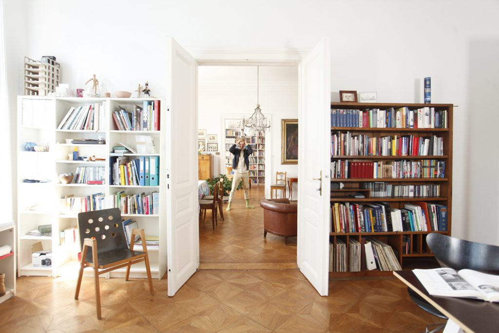 Mann in weißer Hose in Wohnung mit vielen Büchern