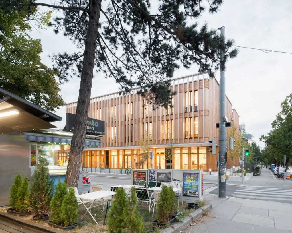 wooden building with lights in the groundfloor and trees in the foreground