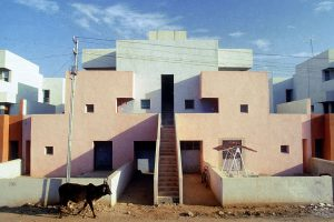 Kuh vor rosa-weißem Gebäude