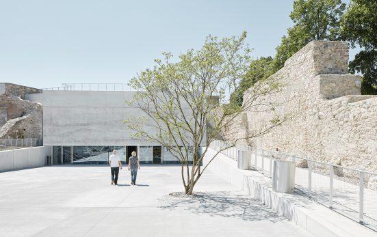 2 Personen auf sehr hellem Platz mit Bäumchen und Mauer rechts daneben