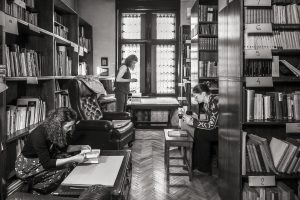 black white photo with 3 women in a library