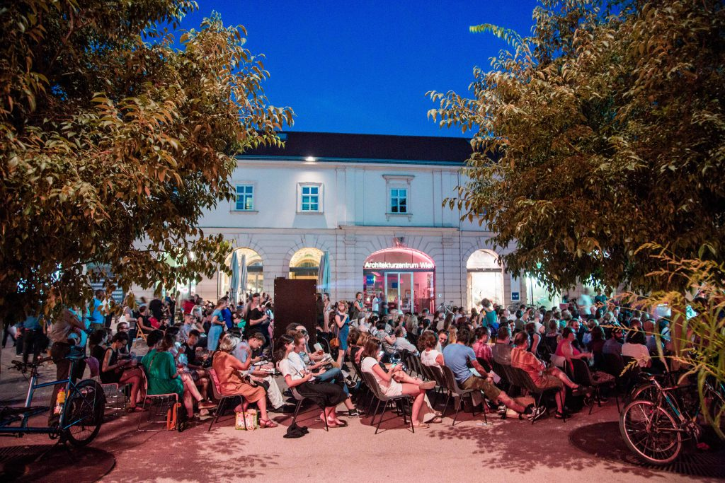 Many people in a courtyard sitting on chairs