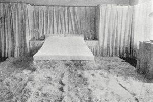 Doppelbett mit Vorhang dahinter und Fellteppich