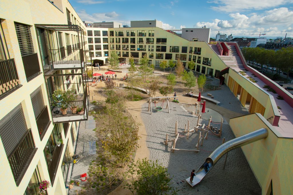 Wohngebäude mit Spielplatz und großer Rutsche