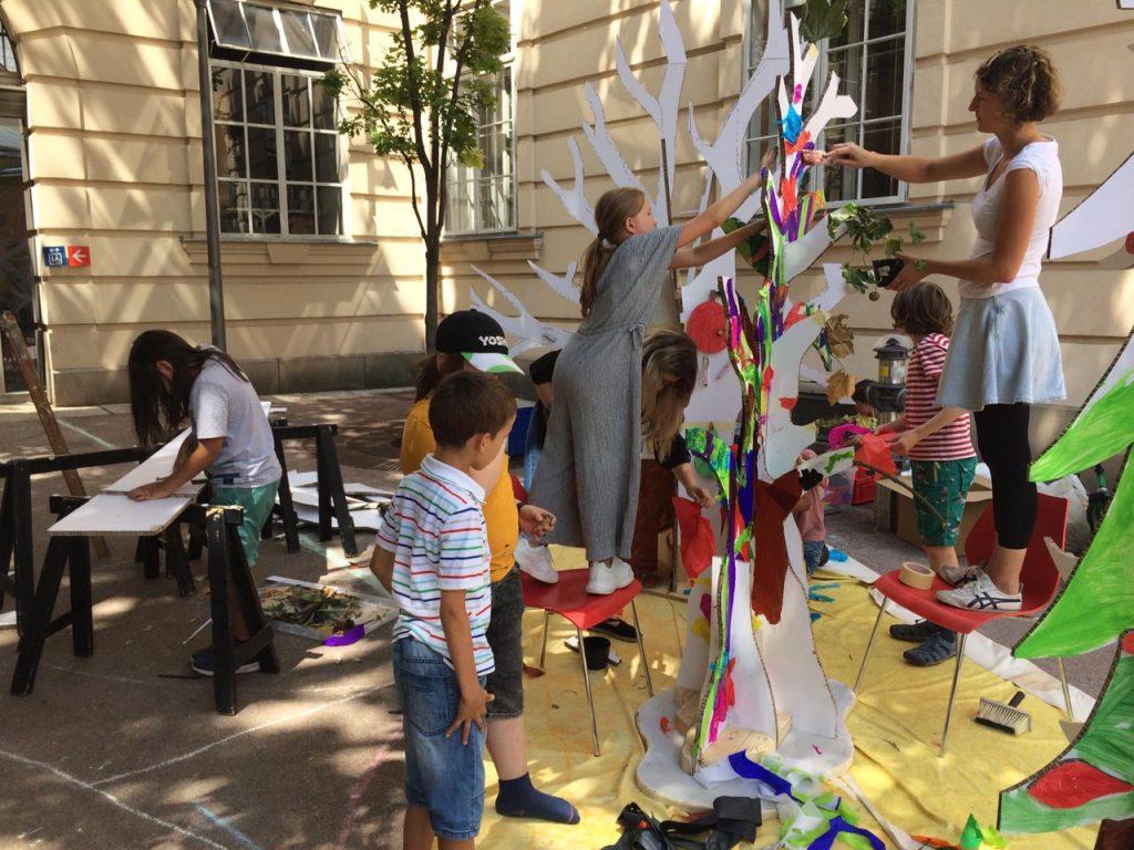 Kinder basteln einen Baum aus Karton und bemalen ihn