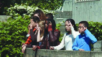 Sieben Jugendliche mit erhobener linker Hand