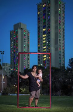 woman with child in her arms in front of skyscrapers holding a red frame