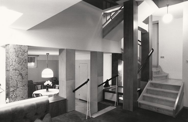 Interior photo black and white with open staircase, lamp and round table