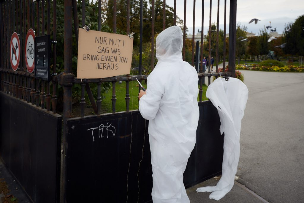 A person in a white full body suit in front of the park gate