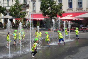 Kinder in Schutzwesten auf einem Platz mit Wasserbespielung
