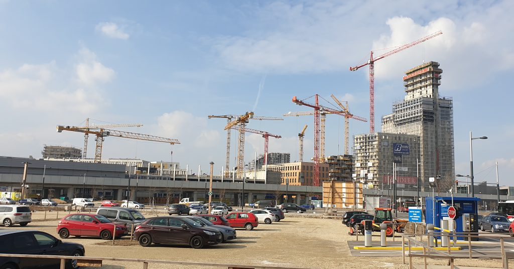 Ten construction cranes in front of a construction site with a large parking lot