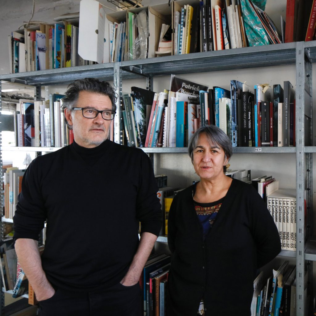 1 man with glasses and 1 woman, both dressed in black