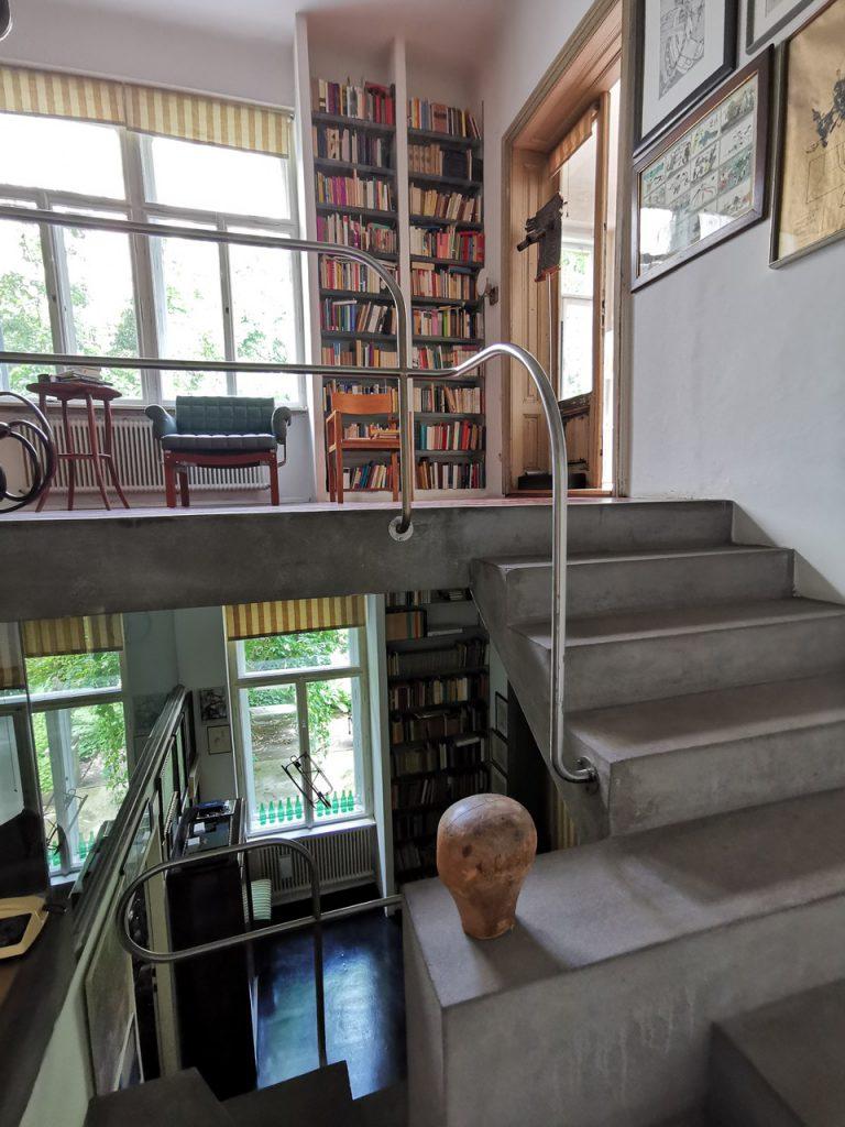 Wohnhaus mit offenem Stiegenhaus, großem Bücherregal und vielen Fenstern