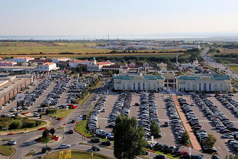 viele Autos auf einem Parkplatz mit Häusern dazwischen