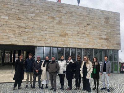 Elf Personen vor einem Gebäude aus Steinziegeln