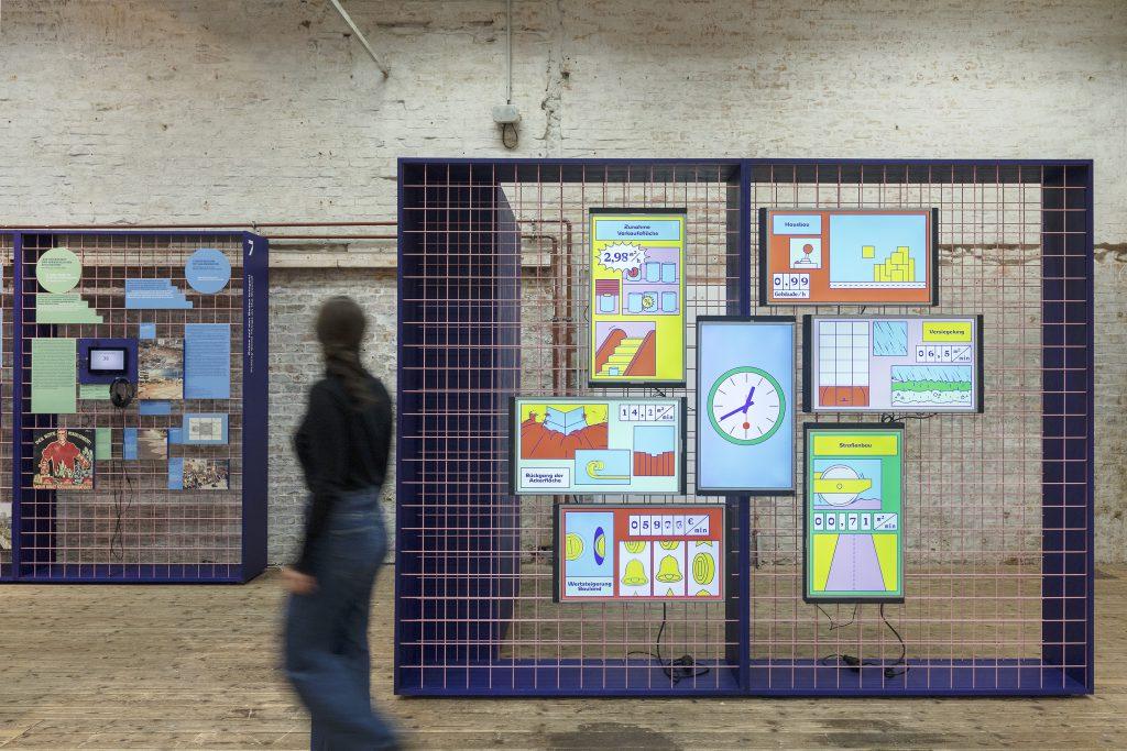 Frau geht in einer Ausstellung vor Wänden mit bunten Bildern